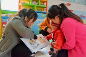 A baby reading with two adults